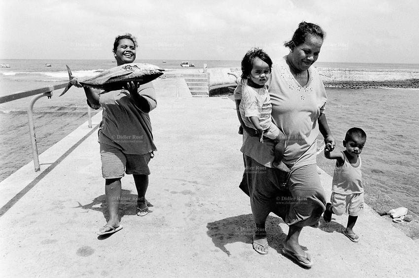 Republic of Nauru. Central Pacific. Nauru is a tiny island (21 square-km). A mother holds a daughter in her arm and a son in her hand. Her friend holds in both her hands a fresh tuna fish which they bought to fishermen in the harbour. © 1999 Didier Ruef