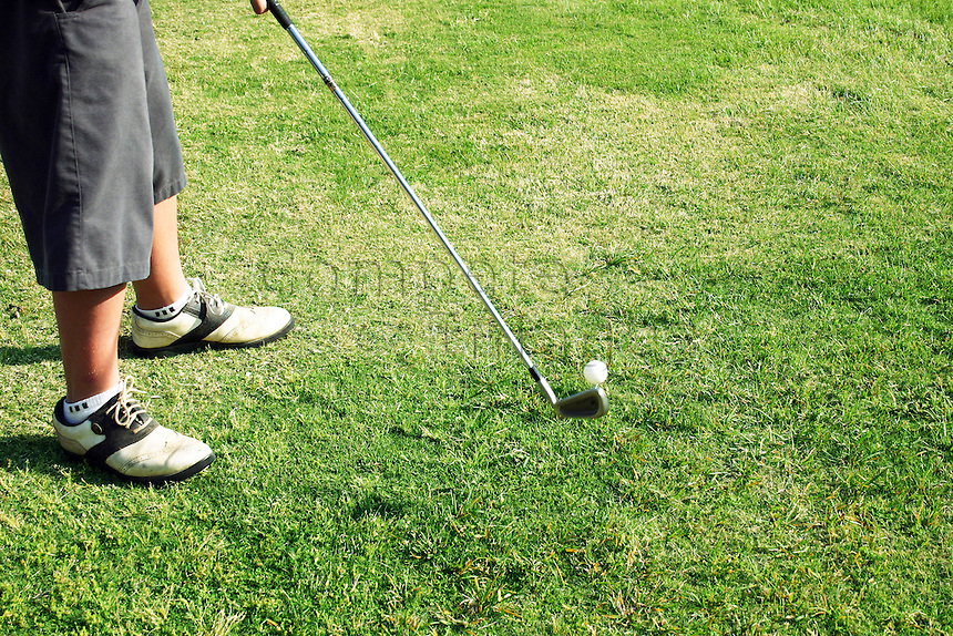 Young golfer takes his iron club back for drive from tee