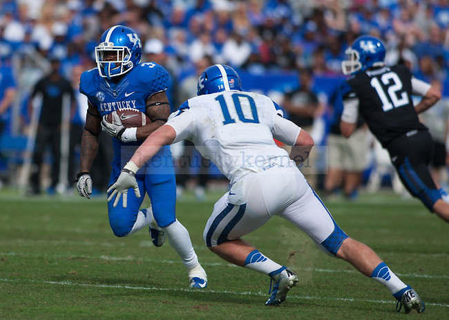 Running back Jojo Kemp (3) runs past linebacker Tyler Brause (10) during the Blue/White Spring Game in Lexington, Ky., on Saturday, April 26, 2014. Blue defeated White 38-14. Photo by Adam Pennavaria | Staff