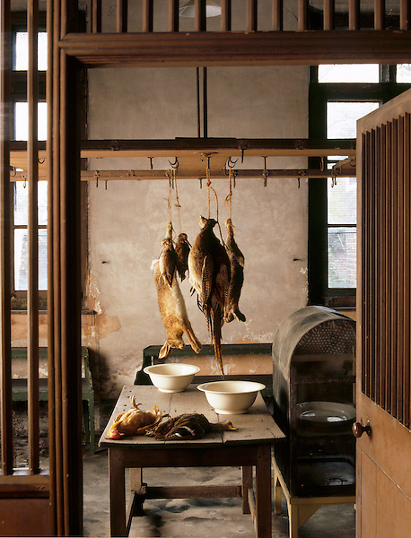 The game larder at Dunham Massey with various game birds, a hare, and a rabbit hanging or on the table.