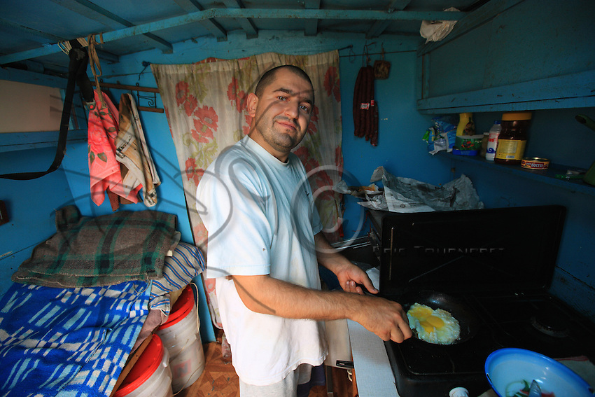 "In the early morning, in the sleeping quarters set up in his ""lodge"", Onéa Dinu Calin, 35 years old, prepares breakfast.  A third-generation beekeeper, he lives in the Maramures and migrates during four months, from April through the end of July."