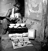 A soldier of the ROK Army eating lunch in a war-destroyed house in Munsan-ni, Korea, as a field ration made in Japan for the ROK Army is shown unpacked.  July 17, 1951.  G. Dimitri Boria. (Army)<br /> NARA FILE #  111-C-6560<br /> WAR &amp; CONFLICT BOOK #:  1473