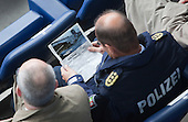 """MSV Arena, Duisburg, North Rhine-Westphalia, Germany - A high-ranking police officer from North Rhine-Westphalia is studying an article from the German mangazine """"Der Spiegel"""" during the commemorative service. A commemorative service is held on the 1st anniversary of the Loveparade tragedy in which 21 young people lost their lives and hundreds were injured as they tried to get to the event to celebrate life, love and music; to date, politicians, organisers and police still try to apportion blame, Photo Credit: Bettina Strenske"""