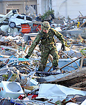March 14, 2011, Sendai, Japan - A Japan Ground Self-Defense Force trooper shifts through the debris as search-and-rescue operations are launched near Sendai Airport, Miyagi prefecture, on Monday, March 14, 2011. The airport, located along the Pacific coast, was flooded by a 10-meter tsunami following a powerful earthquake with a magnitude of 9.0 that jolted northeastern Japanese cities on March 11, 2011. The death toll could reach 10,000 in the nation's worst and the world's fourth worst earthquake. (Photo by Natsuki Sakai/AFLO) [3615] -mis-..