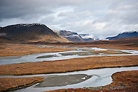 River flows through scenic mountain valley along Kungsleden trail, Lapland, Sweden
