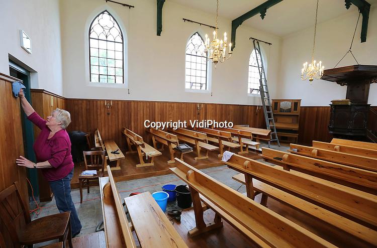 Foto: VidiPhoto<br /> <br /> HOMOET - Voorjaarsschoonmaak begonnen. Een van het kleinste kerkjes van Nederland, de hervormde kerk in het buurtschap Homoet in de gemeente Overbetuwe, krijgt zaterdag een grote poetsbeurt door een ingehuurd schoonmaakteam. De ruimte was door achterstallig 'onderhoud' flink vervuild en de kerkelijke gemeente heeft geen vrijwilligers genoeg om het lastige karwei te klaren (het plafond is 8 meter hoog). Het kerkje staat tussen de boerderijen en koeien op een terp en diende in het begin van de 19e eeuw als 'vluchtheuvel' voor boeren bij hoogwater. Slechts eenmaal in de maand wordt er nog een kerkdienst gehouden. Eigenaar is de hervormde gemeente Valburg-Homoet.