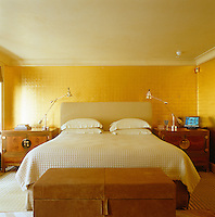 In the master bedroom the contemporary bed is flanked by a pair of Chinese chests and the wall has a gilded appearance
