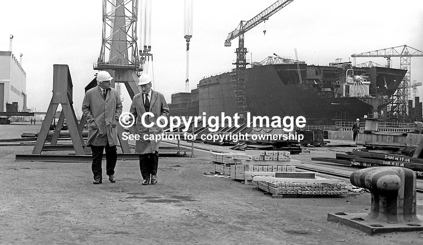 Lord Rochdale, outgoing chairman, Harland &amp; Wolff shipyard, Belfast, N Ireland, left, briefs his successor, Sir Brian Morton, during a tour of the shipbuilding complex. 4th November 1975. 197511040713LR3<br />