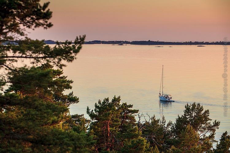Spegelblankt hav med segelbåt i skymning i stockholms skärgård..