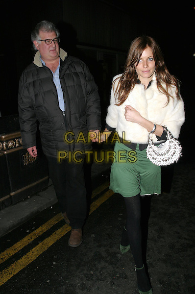 SIENNA MILLER.leaving Gypsy Of Chelsea gala performance at the Royal Court Theatre, Sloane Square.15 March 2004.full length, full-length, holding hands, green skirt, fur jacket, bauble handbag.www.capitalpictures.com.sales@capitalpictures.com.© Capital Pictures.