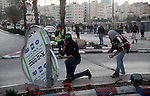 Palestinian demonstrators clash with Israeli forces near the Jewish settlement of Beit El, in the West Bank city of Ramallah, on December 13, 2018. A Palestinian shot dead two Israeli soldiers at a bus stop in the occupied West Bank, the military said, sparking raids in the West Bank city of Ramallah in which one Palestinian was killed. The attack came hours after security forces killed two Palestinian murder suspects, with fears of wider unrest. Photo by Ahmad Arouri