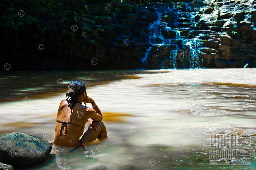 Teenage girl relaxing in waterfall pool at Twin Falls, Haiku, Maui