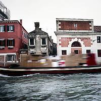 Venezia: un barcone carico di pacchi viaggia in un canale..Venice: a boat load of parcels traveling in a channel