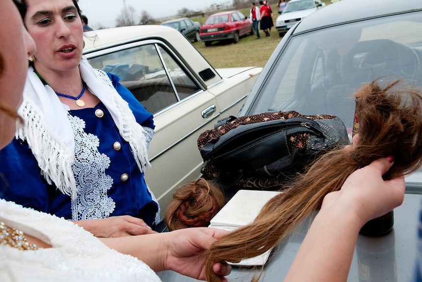 Women from the Tinsmith's gypsy clan buying long human hair at the open air bride market, near Mogila, Stara Zagora.Long hair is a highly prized among young unmarried gypsy girls. At the open air Tinsmiths bride market human hair can be found for 800 lv (400 Euros) per kilogram.