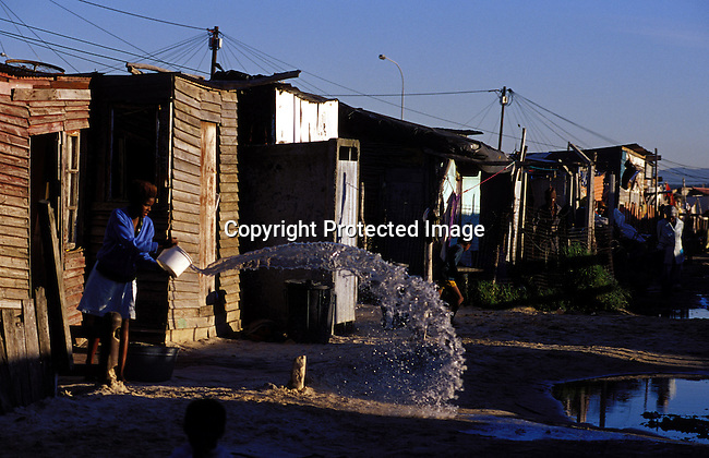 ditown00243 .Digital. Township A woman pouring out water in the street on July 22, 2001 in Site B Khayelitsha, a township about 35 kilometers outside Cape Town, South Africa. Pools of water outside the shacks, gravel road, electricity poles, poverty.©Per-Anders Pettersson/iAfrika Photos.