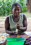 """A woman removes the kernels from corn in Chisatha, a village in southern Malawi. Her community has been hard hit by drought in recent years, leading to chronic food insecurity, especially during the """"hunger season,"""" when farmers are waiting for the harvest."""