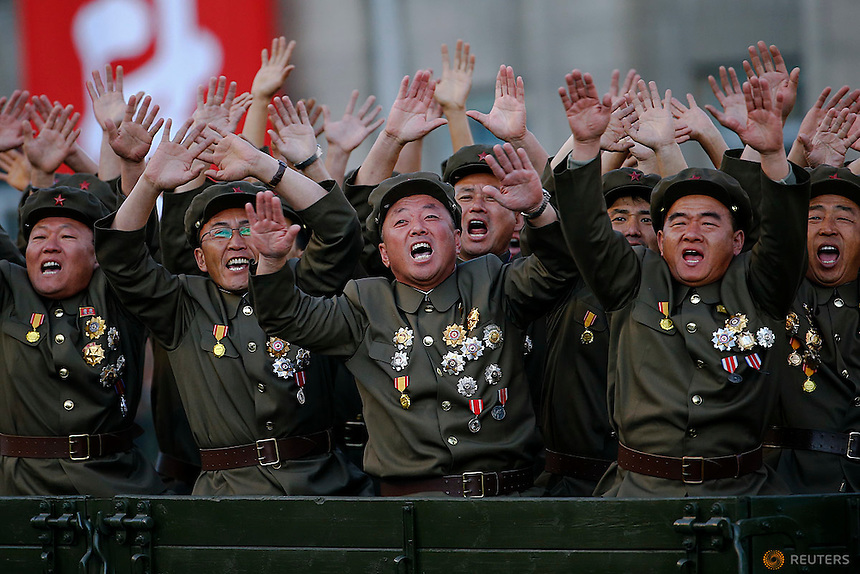 Veteran soldiers react as their truck drives past a stand with North Korean leader Kim Jong Un during the parade celebrating the 70th anniversary of the founding of the ruling Workers' Party of Korea, in Pyongyang October 10, 2015. Isolated North Korea marked the 70th anniversary of its ruling Workers' Party on Saturday with a massive military parade overseen by leader Kim Jong Un, who said his country was ready to fight any war waged by the United States.   REUTERS/Damir Sagolj