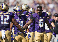Deontae Cooper (6) and Myles Gaskin congratulate Dwayne Washington after the second of Washington's touchdowns.