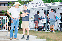 """Huffington Post reporter Maxwell Strachan interviews farmer Kyle Gilchrist (cowboy hat) of Douds, Iowa, at the Iowa State Fair in Des, Moines, Iowa, on Sun., Aug. 11, 2019. Gilchrist was concerned about what an increasing minimum wage means for paying his farm workers. Gilchrist said he didn't vote for Trump in 2016 and instead wrote in Chris Christie's name """"because he believes in small government,"""" Gilchrist said."""