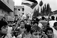 State of Palestine. West Bank. Balata Camp. Palestinian refugees. Young men and boys with olive trees' branches hold a peace demonstration before the opening in Madrid of first round of talks between Israel and the Arab World. The Madrid Conference was a peace conference, held from 30 October to 1 November 1991 in Madrid. It was an attempt by the international community to revive the Israeli–Palestinian peace process through negotiations, involving Israel and the Palestinians as well as Arab countries. Balata Camp is a Palestinian refugee camp established in the northern West Bank in 1950, adjacent to the city of Nablus. It is the largest refugee camp in the West Bank. Balata Camp is densely populated with 30,000 residents in an area of 0.25 square kilometers. In 1991, Balata Camp was living under Isreal's occupation and rules as part as the Occuppied Territories. In the 1980s and 1990s, Balata residents played a leading role in the uprisings known as the First Intifada and the Second Intifada. Balata Camp is since 1993 under palestinian authority, located in the A zone. The Palestinian National Authority (PA or PNA) was the interim self-government body established to govern Areas A and B of the West Bank as a consequence of the 1993 Oslo Accords. Following elections in 2006, its authority had extended only in areas A and B of the West Bank. Since January 2013, the Fatah-controlled Palestinian Authority uses the name State of Palestine on official documents. The Palestinian keffiyeh is a gender-neutral chequered black and white scarf that is usually worn around the neck or head. The Palestinian keffiyeh has become a symbol of Palestinian nationalism. The Palestinian flag is based on the Flag of the Arab Revolt, and is used to represent the Palestinian people. © 1991 Didier Ruef