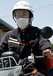 Postman Yoshinori Shoji sets off to deliver letters to an evacuation shelter at the KadonowakiJunior HighSchool in Ishinomaki, Miyagi Prefecture, Japan on Tuesday 24 May 2011..Photographer: Robert Gilhooly