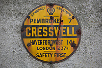 An AA (Automobile Association) sign in Cresswell Quay Pembrokeshire, showing the distance in miles to the towns of Pembroke, Haverfordwest and the city of London. Thursday 16 March 2017