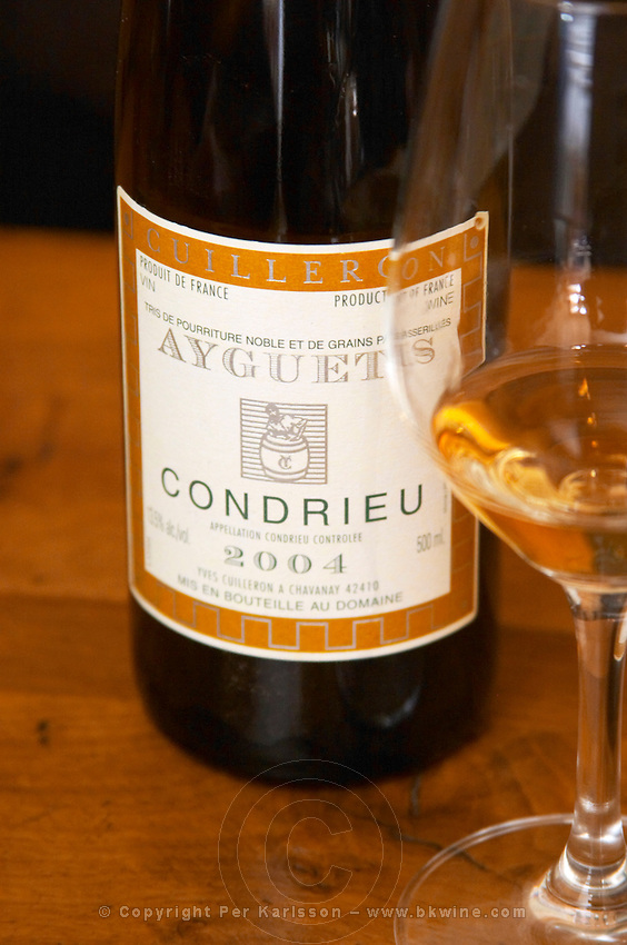 A bottle and a glass of Ayguets Condrieu 2004 - a very unusual sweet Condrieu made from grapes with noble rot (porriture noble) and grapes that were dried before picking (passerille) Domaine Yves Cuilleron, Chavanay, Ampuis, Rhone, France, Europe
