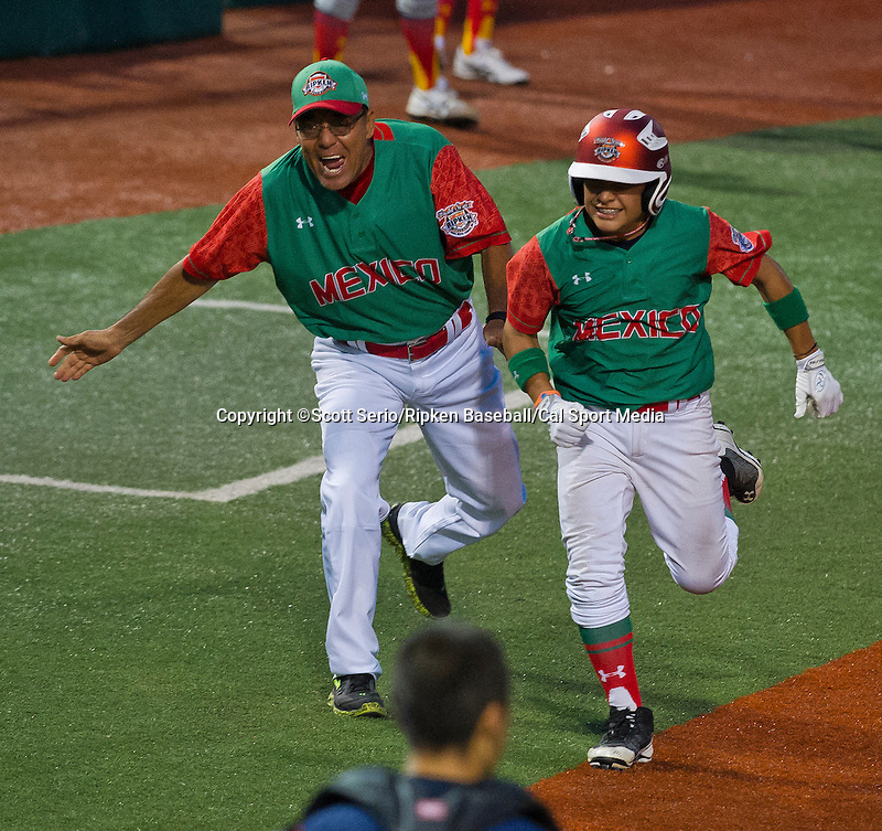 August 15, 2014: Team Mexico's coach congratulates team member on home run against Japan during the Cal Ripken 12u 70-foot World Series United States Championship at the Ripken Experience powered by Under Armour in Aberdeen, Maryland on August 15, 2014, Mexico won 10-7.Scott Serio/Ripken Baseball/CSM