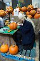 London, UK. 25.10.2014. Young woman carving a pumpkin for Hallowe'en at Borough Market, Southwark. Photograph © Jane Hobson.