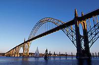 Yaquina Bay Bridge at sunset, with sailboat beneath arch