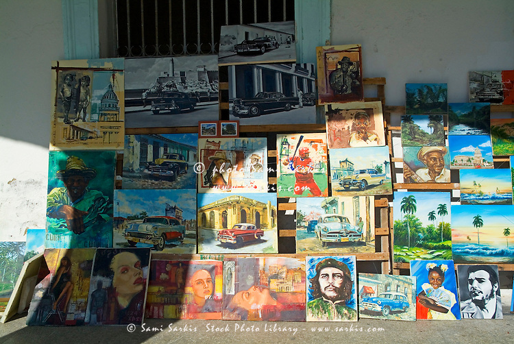 Paintings for sale displayed in a stack on a city street, Santa Clara, Cuba.