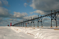 The snow piles up against the pier in Grand Haven, Michigan where a tower light and a piierhead lighthouse sit and when both lights are lined up provides the coreect path into harbor, Ottawa County, MI