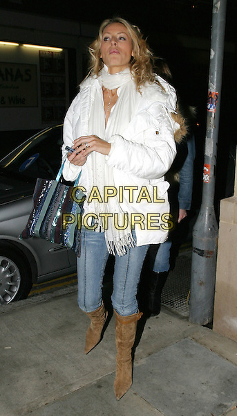 TESS DALY.leaving The Christmas Show in Covent Garden.9 December 2003.full length, full-length, denim jeans, suede knee high boots, white parka jacket, scarf, handbag, funny face.www.capitalpictures.com.sales@capitalpictures.com.© Capital Pictures.
