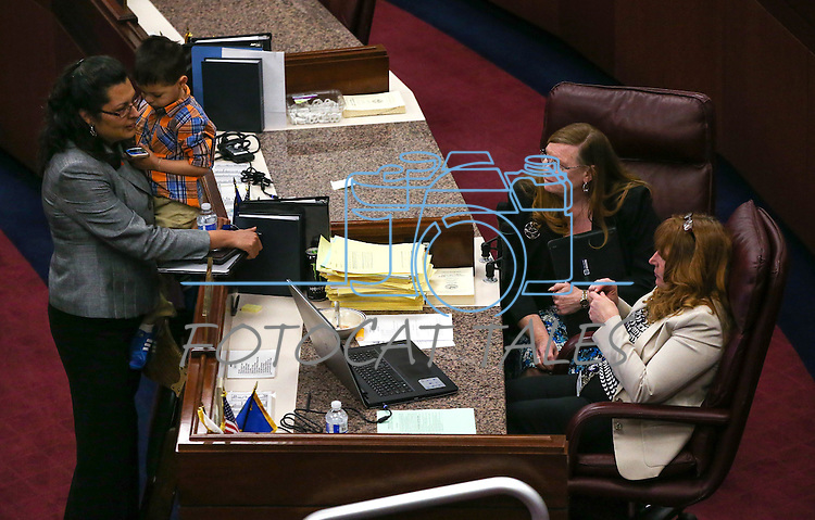 Nevada Assembly Democrats Olivia Diaz, with her son Xavier, Maggie Carlton and Marilyn Kirkpatrick work on the Assembly floor at the Legislative Building in Carson City, Nev., on Friday, May 1, 2015.<br /> Photo by Cathleen Allison