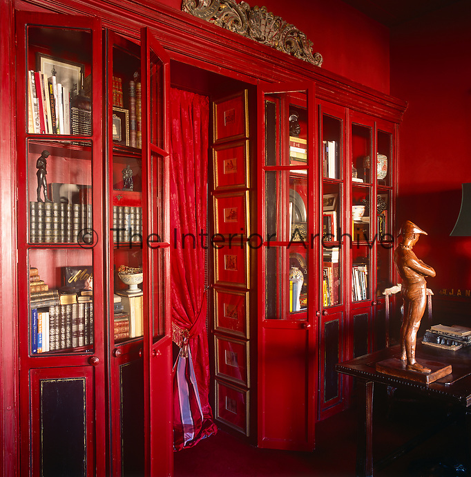 A study painted decorated in a bold deep red colour. A collection of books and figurines are displayed in a tall bookcase.