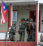 WATERBURY,  CT-051719JS12-  Waterbury police  enter a home on East Liberty Street on Friday as part of a city-wide operation. Waterbury Police, with cooperations State Police, Watertown Police, the States Attorney's Office, the DEA and ATF, conducted search and seizures as well as searching for wanted suspects who police say were suspected in the sale of heroin.<br /> Jim Shannon Republican American