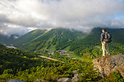 A hiker takes in the view of Franconia Notch State Park from Bald Mountain in the White Mountains, New Hampshire.