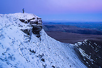 Female hiker on snow covered summit of Corn Du at dawn, Brecon Beacons national park, Wales