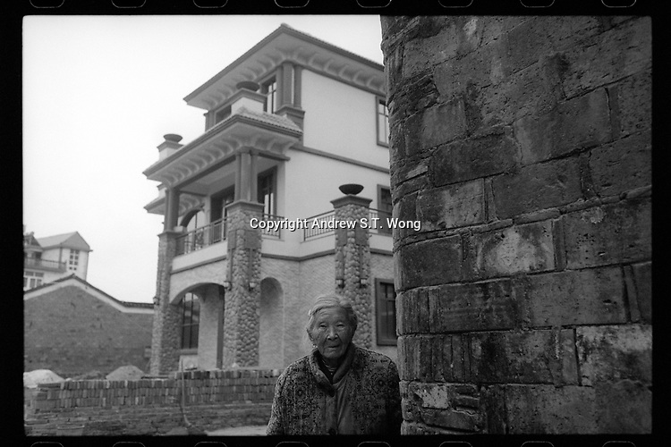 A villager stands in front of a newly built house in Poyang county at Poyang Lake, Jiangxi Province, November 2017. Poyang Lake, located in the north of Jiangxi Province, is the largest freshwater lake in China. It fluctuates dramatically between wet and dry seasons, from 3,500 square kilometres down to about 200 square kilometres. The lake provides a habitat for half a million migratory birds.