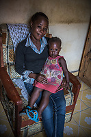 Uganda, Hoima. Hope Lydia Businge, 26 years, has a two year old daughter and runs a hair salon. At home she uses a BioLite cook stove that charges a light and mobile phone.
