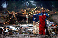 Bruno Sandoval shows a Chilean flag in a flooded area after an earthquake and tsunami in Pelluhue, some 322 kms, about 200 miles, southwest of Santiago, Sunday, Feb. 28, 2010. A 8.8-magnitude earthquake hit Chile early Saturday, Feb. 27. ..Photo by Roberto Candia