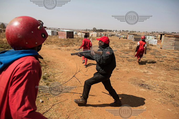 A member of the Red Ants brandishes a shot gun during a so-called 'demolition' operation to clear dwellings and evict squatters from land in Vlakfontein. The violent action resulted in the deaths of two people from among the community being evicted. The Red Ants are a controversial private security company often hired to clear squatters from land and so-called 'hijacked' properties.
