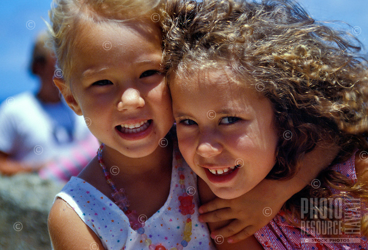 American and Tongan girls playing and smiling at the beach