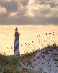 The historic St. Augustine lighthouse on Anastasia Island photographed from a nearby beach at sunset.