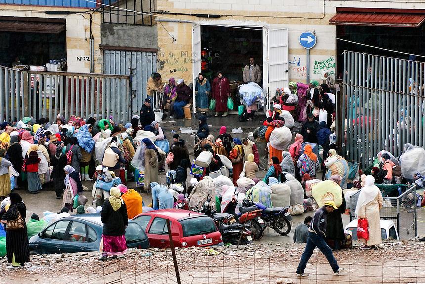 Uomini e donne marocchine affollano l'ingresso de Las Naves, centro commerciale alla periferia di Ceuta, da cui provengono le merci portate in Marocco attraverso il passaggio illegale di El Biutz. Ceuta, 8 febbraio 2010<br /> <br /> Moroccans, men and women, crowded the entrance of Las Naves, the shopping mall near Ceuta border, where they get the goods then they carry in Morocco through El Biutz illegal passage.<br /> Ceuta, February 8, 2010