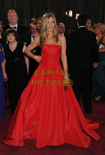Jennifer Aniston (wearing Valentino).85th Annual Academy Awards held at the Dolby Theatre at Hollywood & Highland Center, Hollywood, California, USA..February 24th, 2013.oscars full length red strapless dress gown gold clutch bag hand on hip.CAP/ROT/TM.©Tony Michaels/Roth Stock/Capital Pictures