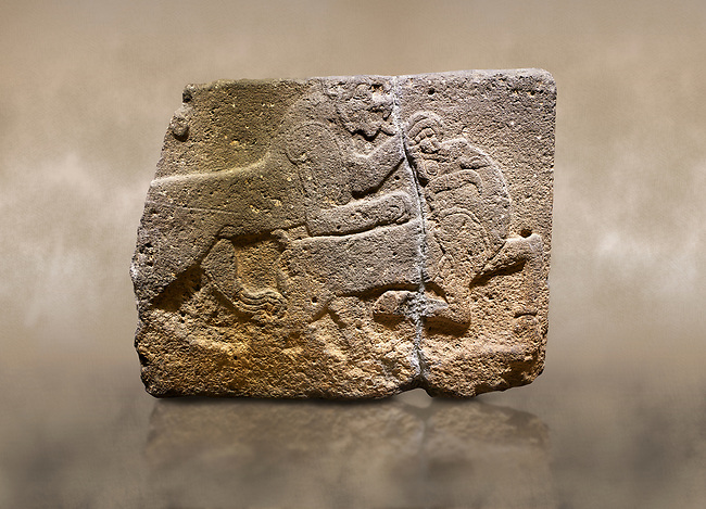 Photo of Hittite monumental relief sculpted orthostat stone panel of a Procession. Basalt, Karkamıs, (Kargamıs), Carchemish (Karkemish), 900-700 B.C. Anatolian Civilisations Museum, Ankara, Turkey. Two animals struggling with each other. The lion attacking the bull holds the bull's chin and turns it backwards.  <br /> <br /> Against a brown art background.