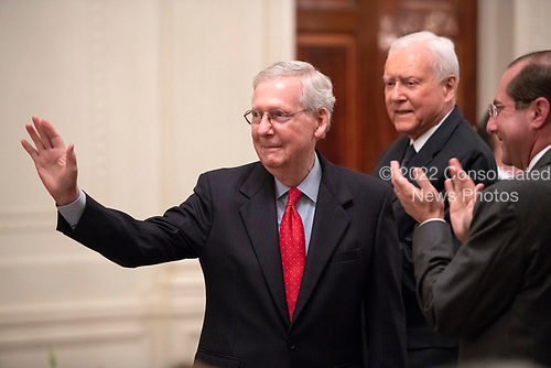United States Senate Majority Leader Mitch McConnell (Republican of Kentucky) acknowledges the applause as he arrives for the ceremonial swearing-in ceremony for Associate Justice of the US Supreme Court Brett Kavanaugh hosted by US President Donald J. Trump in the East Room of the White House in Washington, DC on Monday, October 8, 2018.  Kavanaugh formally took the oath on Saturday, hours after he was confirmed by the US Senate.  Looking on from the right is United States Senator Orrin Hatch (Republican of Utah).<br /> Credit: Ron Sachs / CNP<br /> (RESTRICTION: NO New York or New Jersey Newspapers or newspapers within a 75 mile radius of New York City)