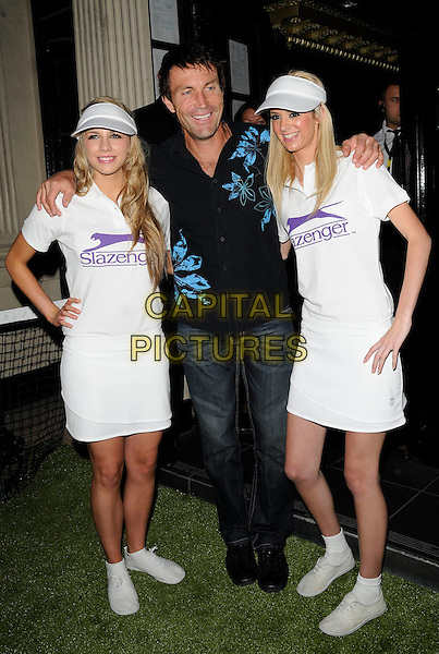 PAT CASH & GUESTS.The Slazenger Party, Movida nightclub, London, England..June 24th, 2010.full length jeans denim blue black shirt print floral arms over shoulders white top top visor hat hand on hip skirt.CAP/CAN.©Can Nguyen/Capital Pictures.