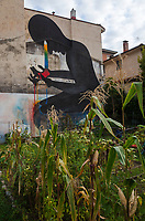 Switzerland. Canton Ticino. Lugano. Street art. The graffiti is on a private house's wall. It is a drawing of a black man on his knees holding a colorful candle in his hands. A private vegetable garden with a corn plantation.13.09.17  © 2017 Didier Ruef